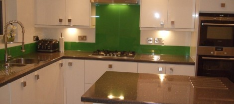 Modern kitchen with granite worktops and glass splash backs installed by Aqua Systems